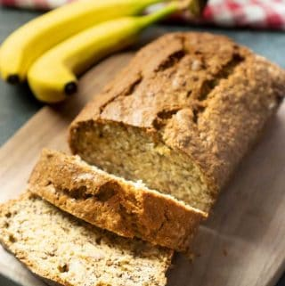 Banana bread with a couple slices cut on a cutting board next to two bananas