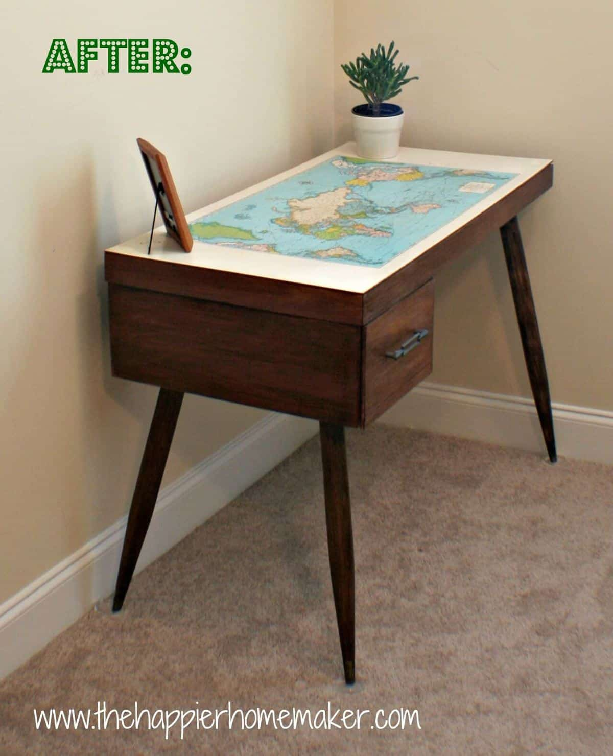 A wooden desk with a map table top with a picture frame and small pant on it
