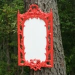 A vintage mirror that has a detailed, red wood frame