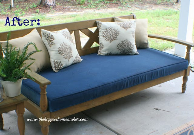 Outdoor patio sofa with navy blue seat cushion and beige and coral cushions