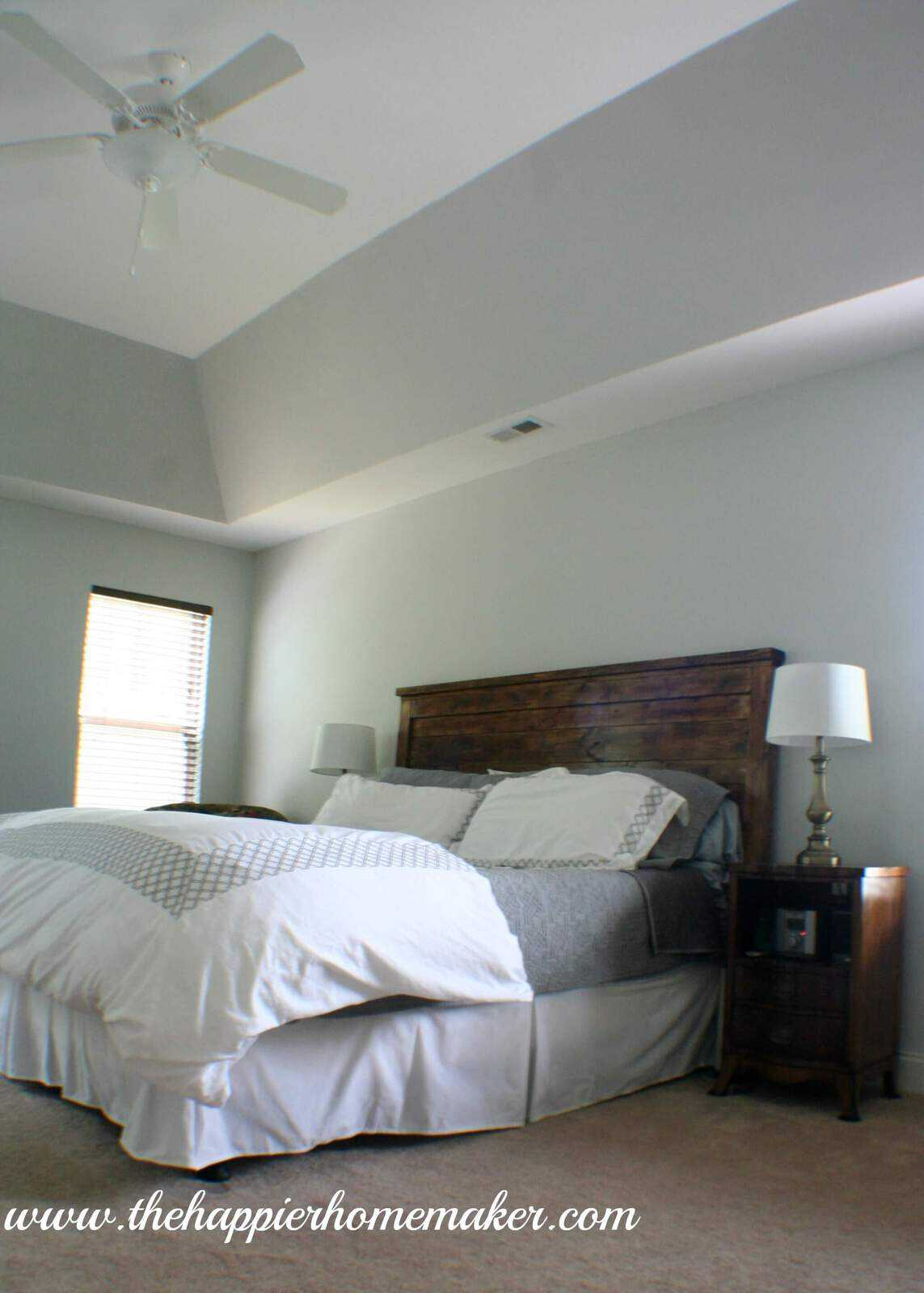 A bedroom with a dark wood headboard and gray bedding