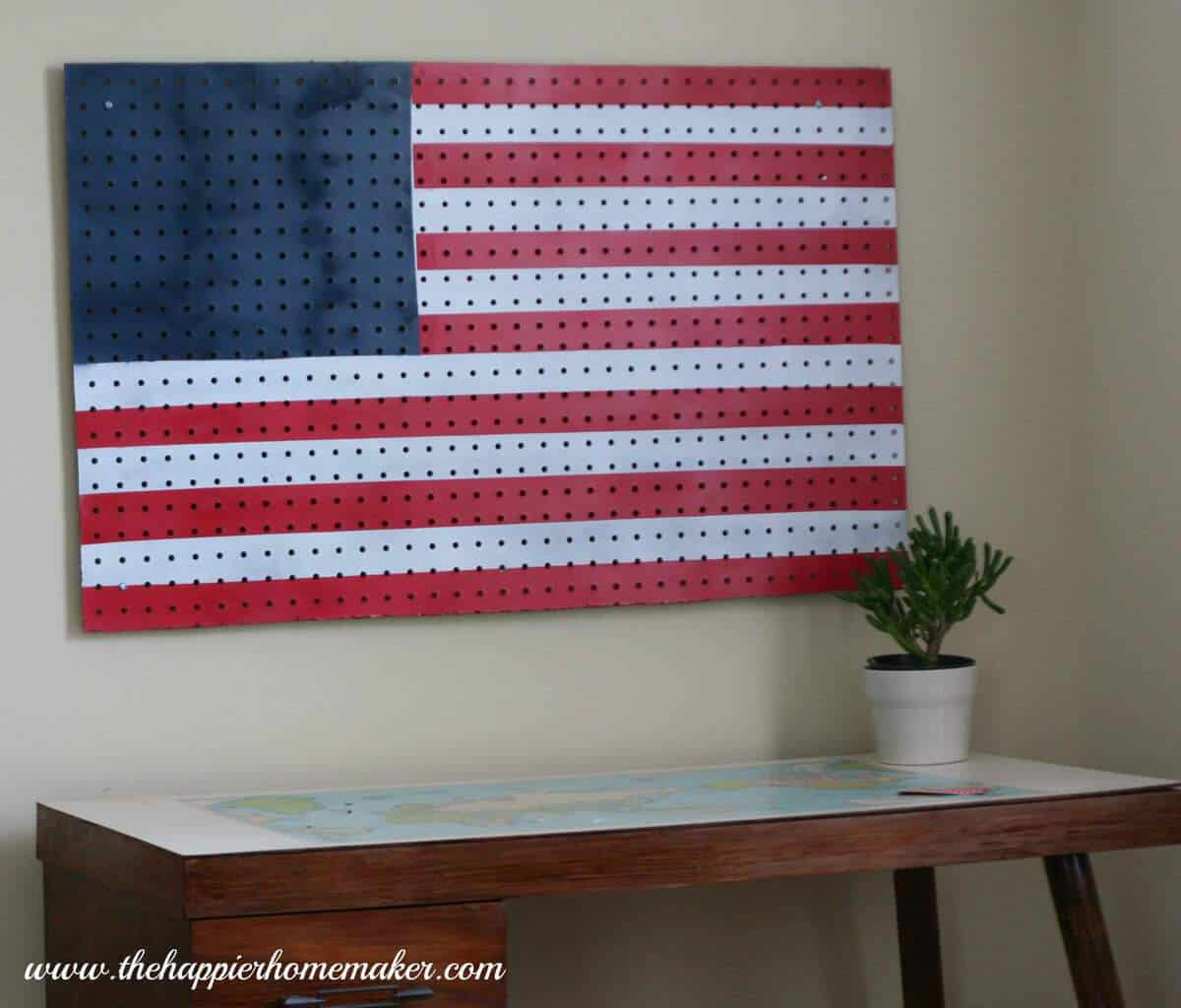 American flag pegboard over a desk with a small plant