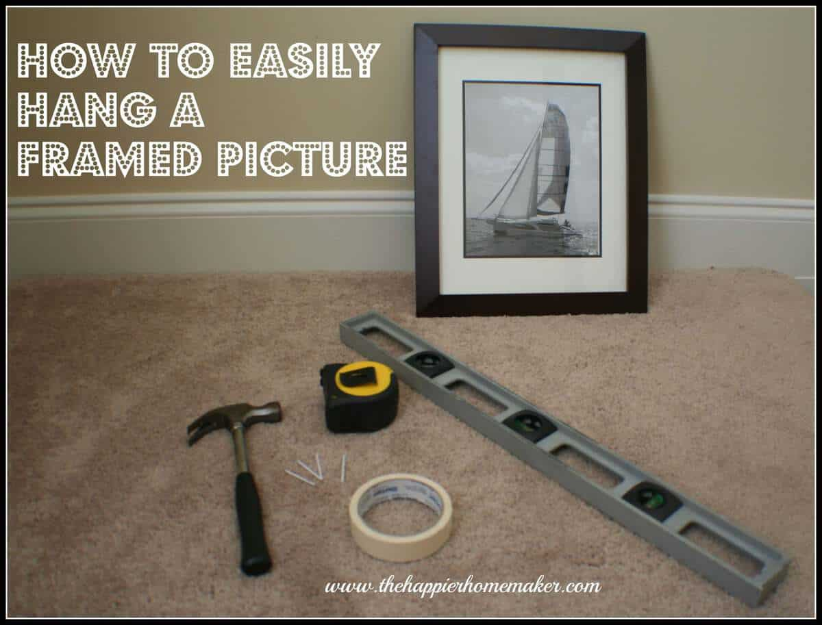 A brown picture frame of a sail boat with a level, hammer, tape measure, scotch tape and nails to hang the picture