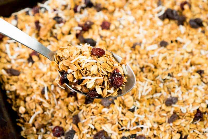 best homemade granola with raisins and dried cranberries on baking sheet