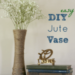 A DIY jute wrapped vase with small white flowers next to a books and a compass