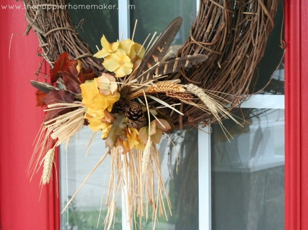 A close up of a grapevine wreath with pieces of flower, wheat and feathers as accents