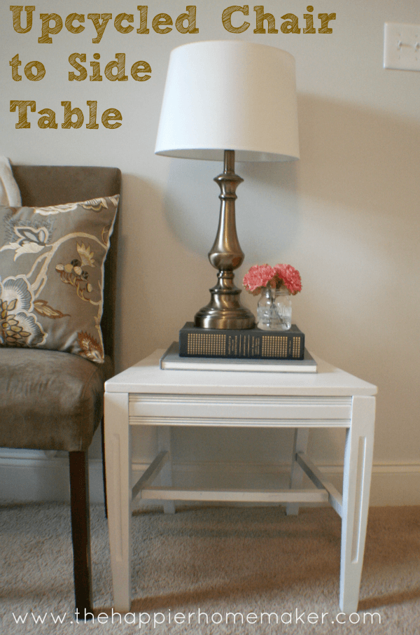 A close up of a white, up-cycled chair to side table  with a lamp and flowers on it