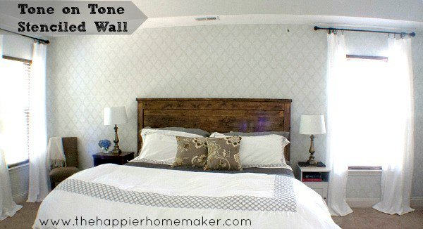 A tone on tone stenciled wall with a bedroom set in front of it