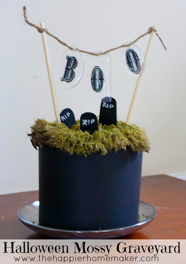 faux fake graveyard with green moss and paper headstones with Boo banner and jute twine