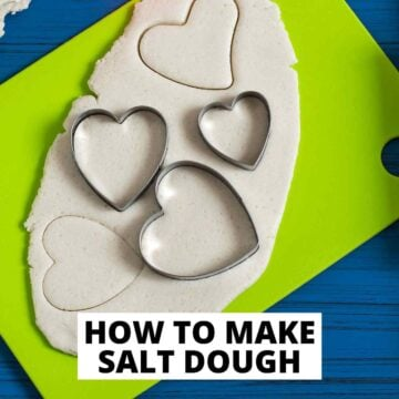 text reading how to make salt dough with green cutting board with salt dough rolled out and three heart shaped cookie cutters on it.