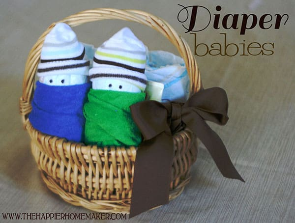 A close up of diaper babies in a wicker basket with a brown bow