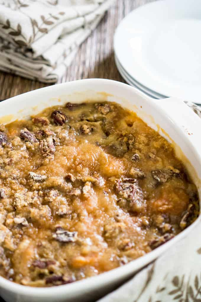 sweet potato casserole with crumble topping in white casserole dish