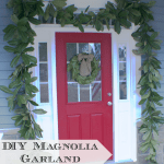 A close up of a red door with magnolia garland around it