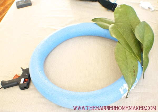 An in process picture of adhering magnolia leaves to a foam wreath form