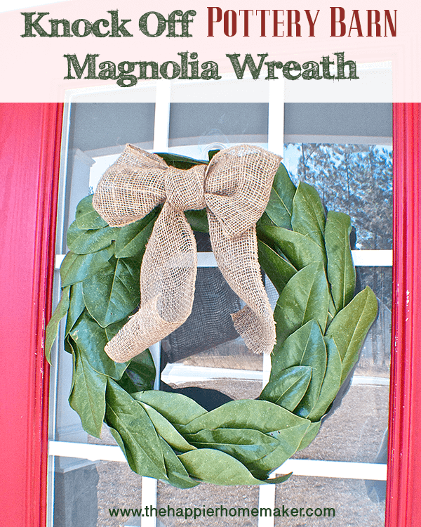 A close up of magnolia leaves decorated as a wreath with a burlap bow