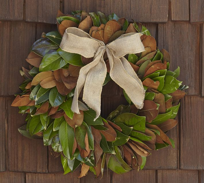 A close up of a Pottery Barn magnolia wreath with brown bow