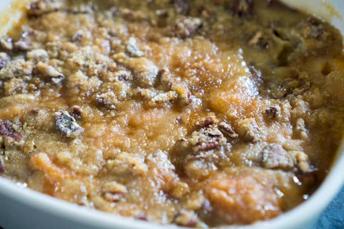 sweet potato casserole recipe in white casserole dish with brown sugar and pecan crumble topping