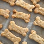 A close up of homemade dog treats sitting on a baking pan