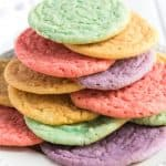 rainbow colored kool-aid cookies stacked on white plate