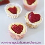 A close up of strawberry heart mini cheesecake bites topped with strawberries cut like hearts on top