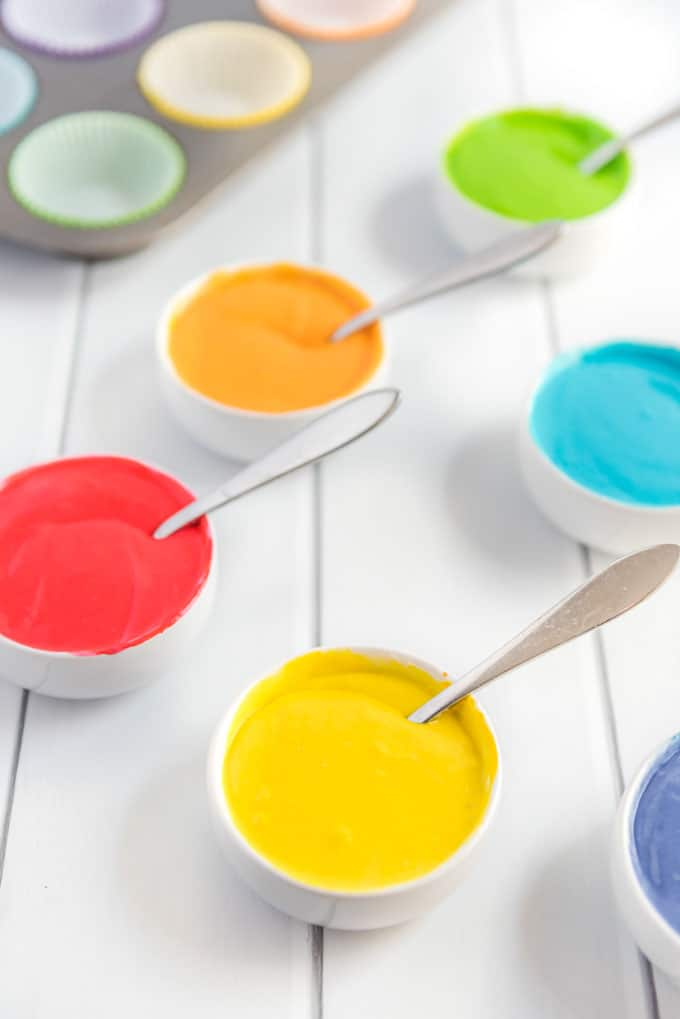 colored cupcake batter in bowls with spoons