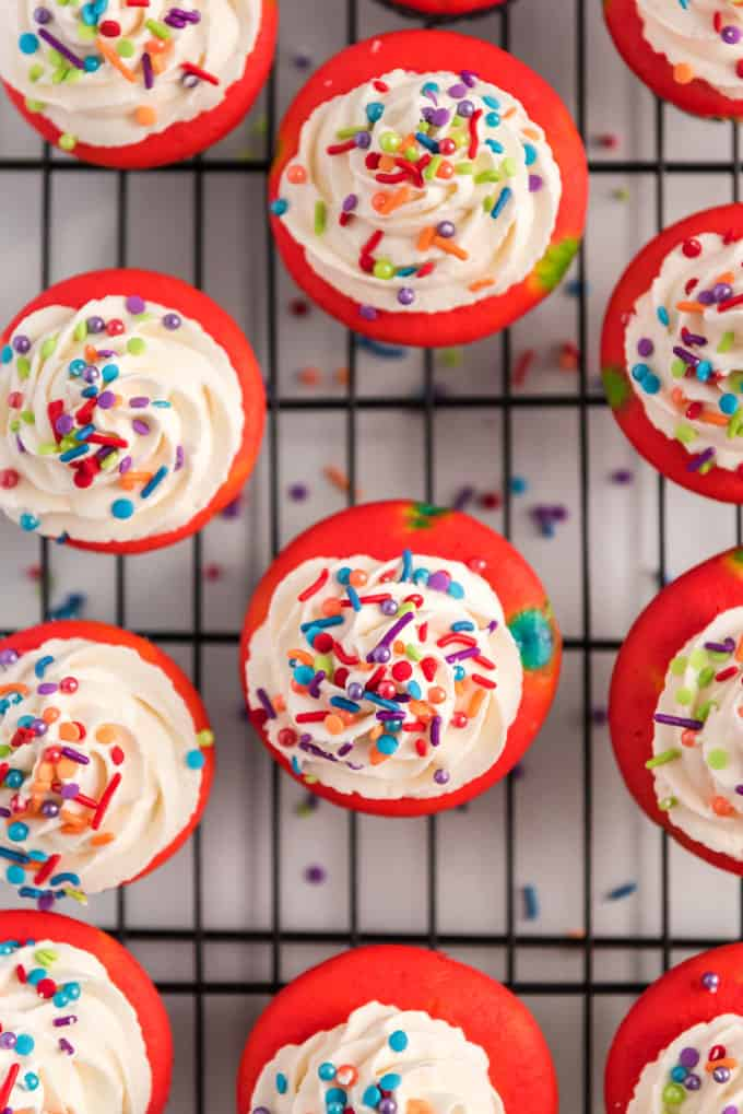 overhead view of colorful rainbow cupcakes with white frosting and sprinkles on cooling rack
