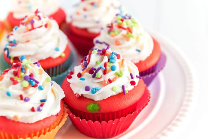 A close up of a rainbow cupcake topped with white icing and sprinkles on white plate