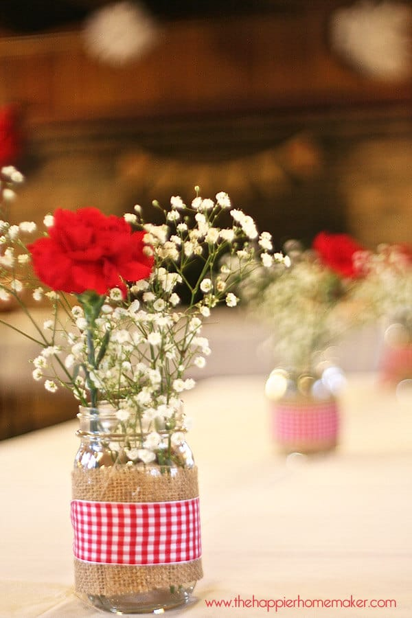 A close up of rustic bridal shower table centerpieces including baby's breath and red carnations