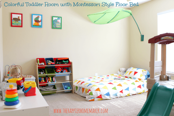 A toddler nursery with a bed with a green fabric leaf over it and storage units