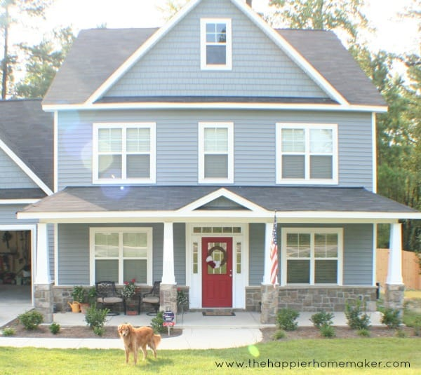blue craftsman three story home with red door and dog in front yard