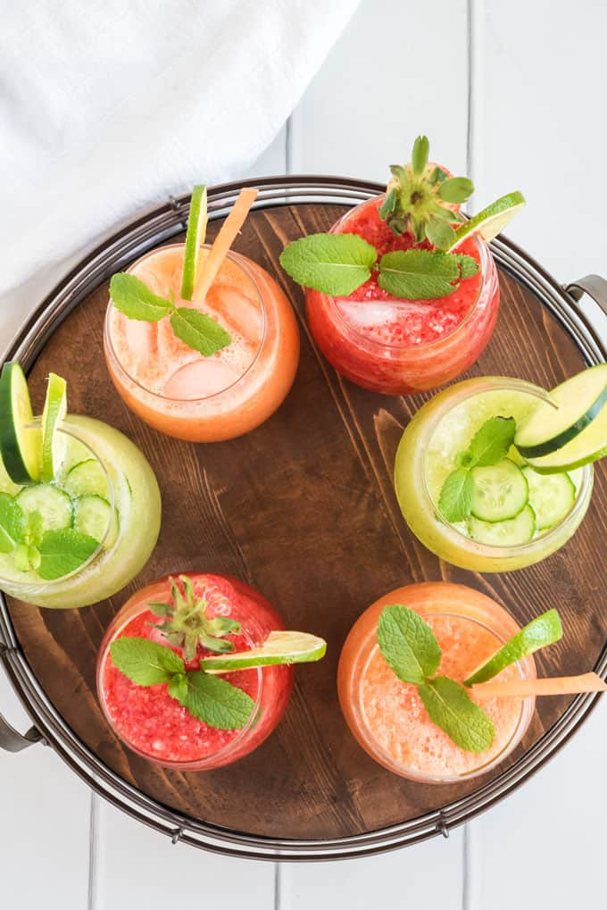 many flavors of agua fresca in glasses on wood tray