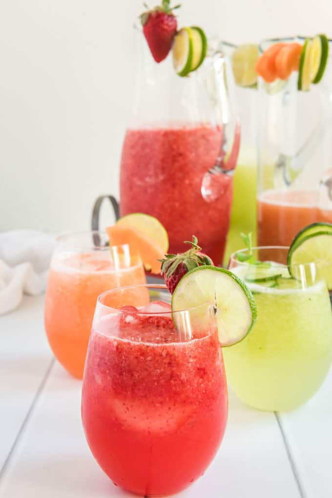 strawberry, cantaloupe and cucumber agua fresca in glasses with pitchers