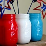 mason jars painted red, white, and blue with patriotic stars on sticks