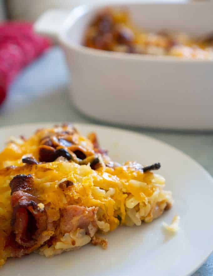 easy cheesy bacon hash brown casserole on a white plate with white casserole dish in background
