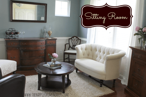 A sitting room with a white sofa, chair, coffee table and brown server