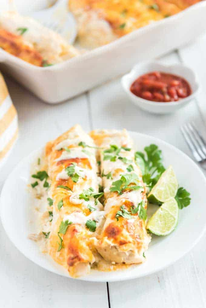 two white chicken enchiladas on a white plate with lime slices and cilantro garnish with fork and salsa