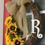 "A close up of a grapevine wreath with fake sunflowers, the letter ""R"" and burlap on a red door"