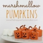 Candy covered marshmallows covered made to look like pumpkins with pieces of pretzel as a pumpkin stem