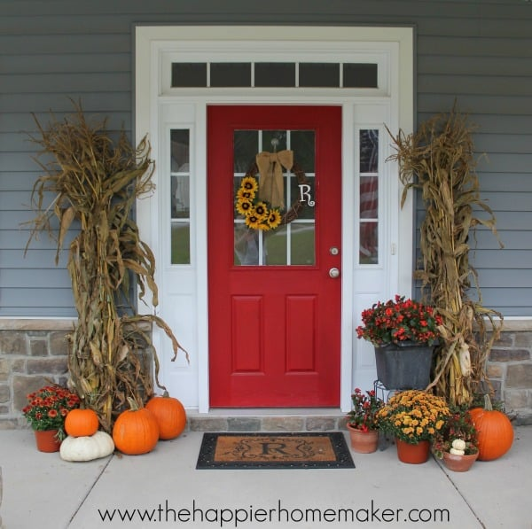 An Autumn porch decoration with dried corn stalks, mums, and pumpkins