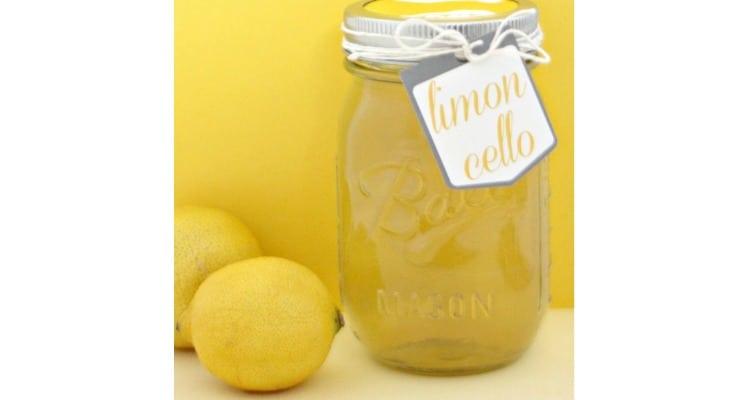 A mason jar full of homemade Limoncello next to lemons