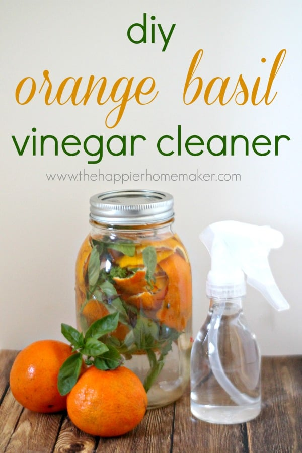 jar with oranges and basil with spray bottle for vinegar cleaner