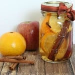 A close up of a clear mason jar filled with simmering pot recipe next to cinnamon sticks, an orange and apple