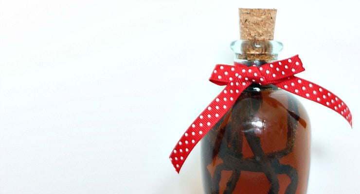 A homemade vanilla extract in clear jar tied with a red and white polka dot ribbon