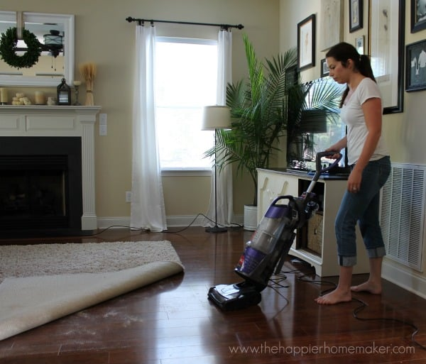 A woman vacuuming underneath of a rug