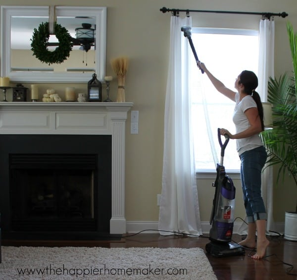 A woman cleaning white curtains in a living room