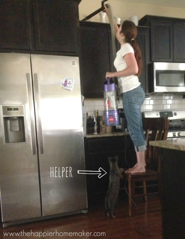 A woman cleaning kitchen cabinets while standing on a chair