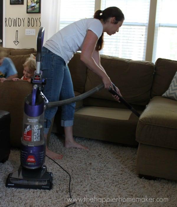 A woman vacuuming in-between sofa cushions