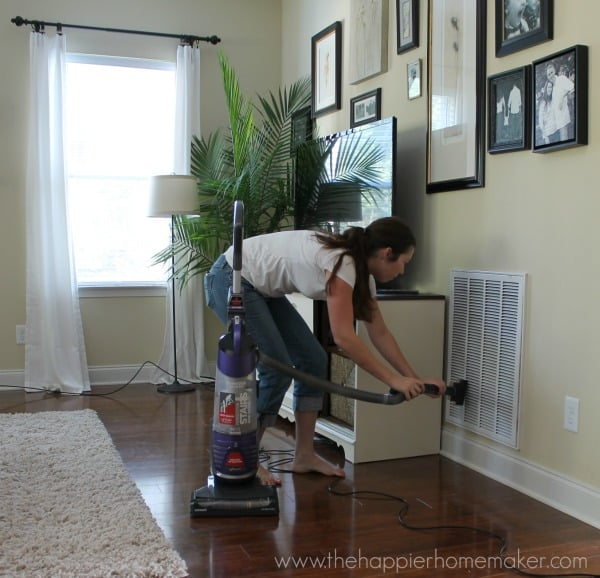 A woman cleaning an HVAC input vent with a vacuum