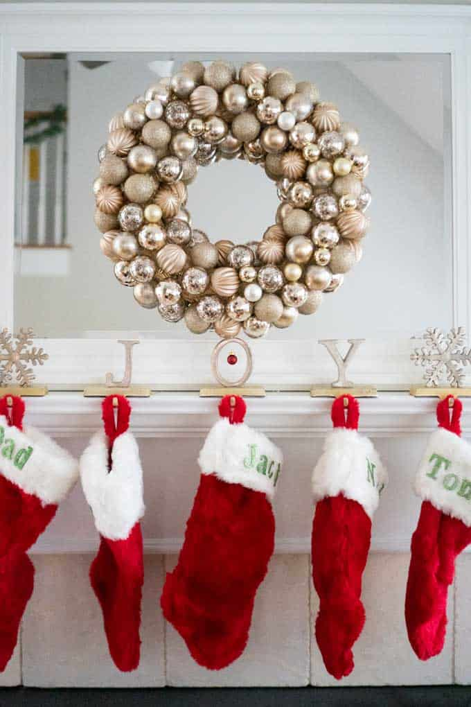 An ornament wreath hanging over a mantel with red Christmas stockings