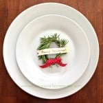A white bowl and plate with a rosemary Christmas wreath place card